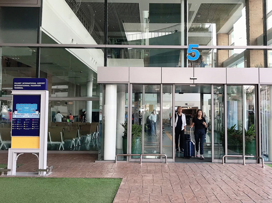 exit 5 car rental pick up point at phuket international airport HKT showing passengers arriving on holiday with suitcases